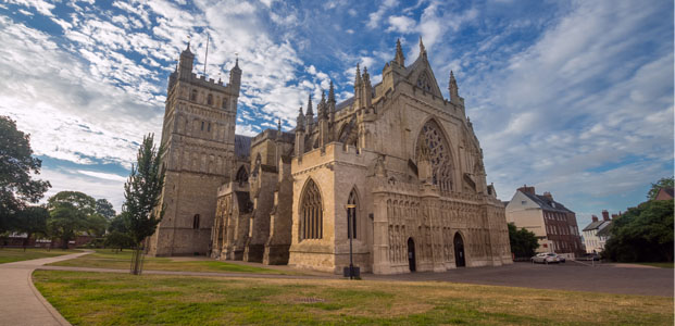 Exeter Cathedral in the West Country set against a cloudy blue sky