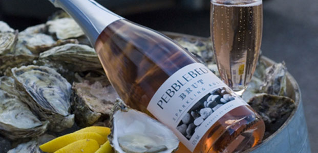 a bottle of West Country Pebblebed rose wine on a bed of oysters