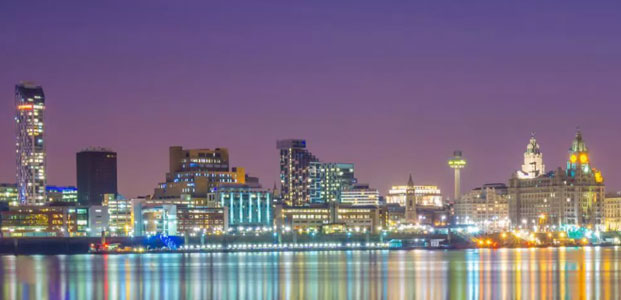Panoramic view of the Liverpool skyline from across the river Mersey. View of Pier Head and the historic waterfront buildings. Modern buildings. Dusk.