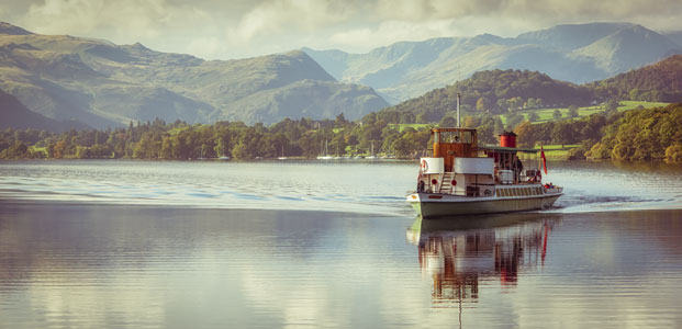 A steamer boat floats on lake Ullswater in the Lake District