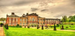 The green lawns and main building of royal Kensington Palace on an overcast day