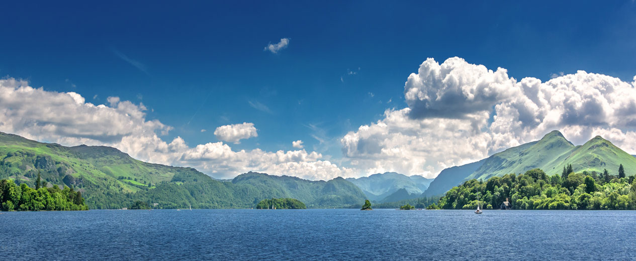 Image of a tranquil lake and under a blue sky in the Lake District