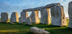 The grey rocks of Stonehenge standing before a blue sky