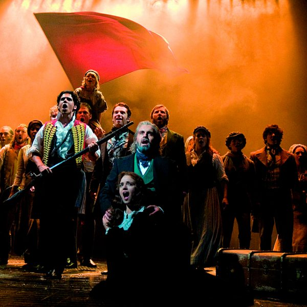 Le Miserables, the stage musical. A full stage scene on the barricades and one of the big moments of the production. Actors, men and women singing. A large red flag as backdrop.