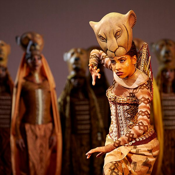 The Lion King musical stage production. A stage number with actors and singers, representing animal characters. Vibrant and exotic costumes. Lion masks.