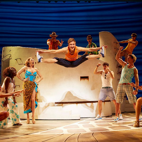 Mamma Mia, the musical stage show based on the songs of Abba. A beach scene, with men and women dancing and singing. A character performing a leap and doing the splits.