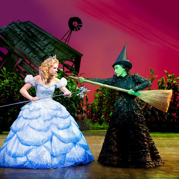 Two characters on stage at the Apollo Theatre in London. A musical stage production Wicked. A wicked witch with a green face and a broomstick, and a princess in her ballgown.